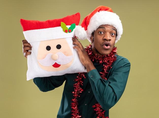 Afroamerikanermann in der weihnachtsmannmütze mit girlande, die weihnachtskissen hält, das kamera betrachtet, die über grünem hintergrund steht