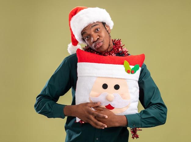 Afroamerikanermann in der weihnachtsmannmütze mit girlande, die weihnachtskissen hält, das kamera glücklich und positiv steht über grünem hintergrund
