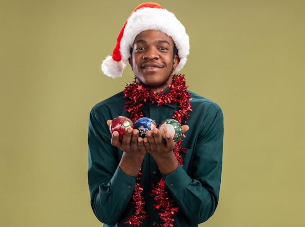 Afroamerikanermann in der weihnachtsmannmütze mit girlande, die weihnachtskugeln hält, die kamera betrachten, die mit glücklichem gesicht über grünem hintergrund steht