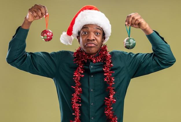 Afroamerikanermann in der weihnachtsmannmütze mit girlande, die weihnachtskugeln hält, die über grüner wand überrascht und verwirrt stehen