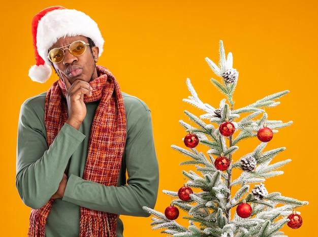 Afroamerikanermann in der weihnachtsmannmütze und im schal um den hals, der kamera mit nachdenklichem ausdruck betrachtet, der denkend steht neben einem weihnachtsbaum über orange hintergrund