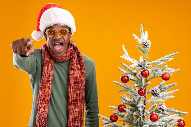 Afroamerikanermann in der weihnachtsmannmütze und im schal um den hals, der mit dem zeigefinger an der kamera zeigt, glücklich und aufgeregt, die neben einem weihnachtsbaum über orange hintergrund stehen