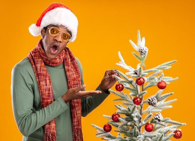 Afroamerikanermann in der weihnachtsmannmütze und im schal um den hals, der neben einem weihnachtsbaum steht, der mit armen präsentiert, die über orange hintergrund überrascht schauen
