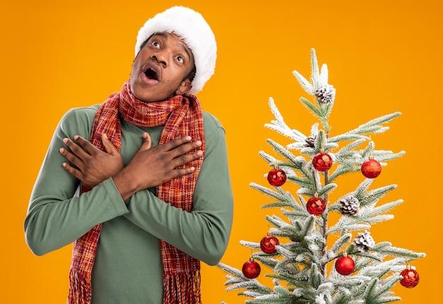 Afroamerikanermann in der weihnachtsmannmütze und im schal um den hals, der oben händchenhalten auf seiner brust überrascht und erstaunt neben weihnachtsbaum über orange hintergrund schaut