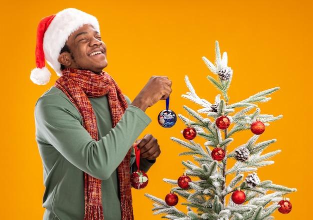 Afroamerikanermann in der weihnachtsmannmütze und im schal um den hals, der weihnachtskugeln auf einem weihnachtsbaum glücklich und fröhlich steht über orange wand hängt