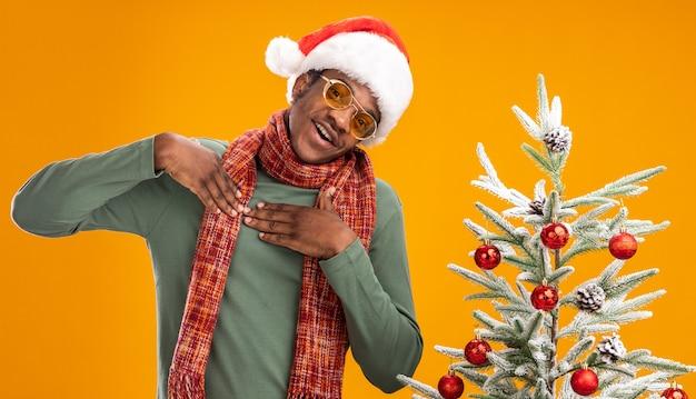 Afroamerikanermann in der weihnachtsmütze und im schal um hals, die hände auf seiner brust glücklich und positiv fühlen dankbar dankbar, neben einem weihnachtsbaum über orange wand stehend