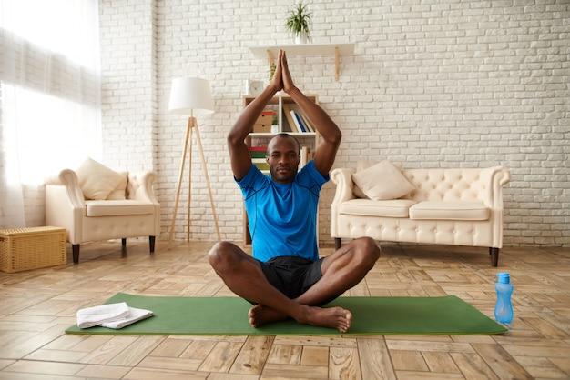 Afroamerikanermann meditiert in der lotoslage.