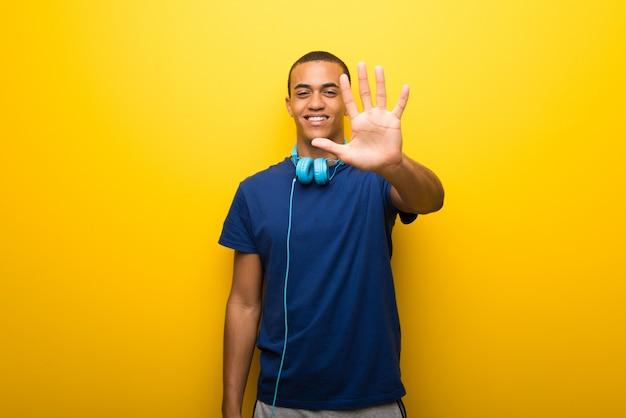 Afroamerikanermann mit blauem t-shirt auf dem gelben hintergrund, der fünf mit den fingern zählt