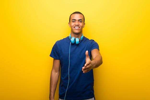 Afroamerikanermann mit blauem t-shirt auf dem gelben hintergrund, der hände für das schließen eines guten deals rüttelt