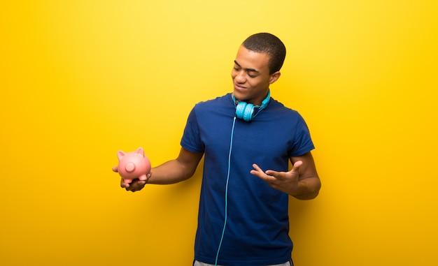 Afroamerikanermann mit blauem t-shirt auf der gelben wand, die ein großes sparschwein hält