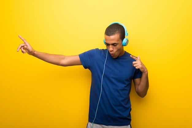 Afroamerikanermann mit blauem t-shirt auf gelb hörend musik mit kopfhörern und tanzen