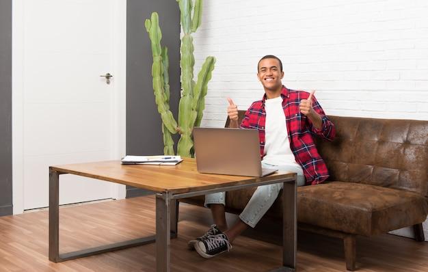 Afroamerikanermann mit dem laptop im wohnzimmer, das daumen gibt, up geste mit beiden händen und dem lächeln