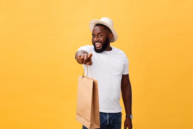Afroamerikanermann mit den bunten papiertüten lokalisiert auf gelbem hintergrund