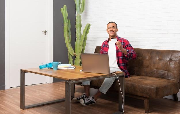Afroamerikanermann mit laptop im wohnzimmer, das eine kreditkarte hält