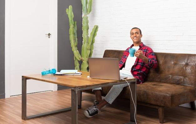 Afroamerikanermann mit laptop im wohnzimmer, das einen heißen kaffee hält