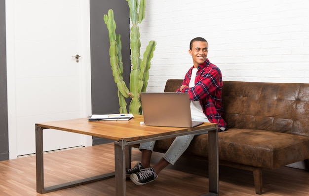 Afroamerikanermann mit laptop im wohnzimmer, das über der schulter mit einem lächeln schaut