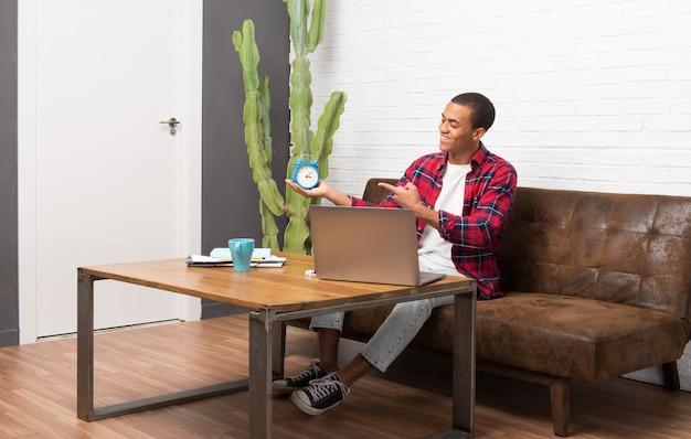 Afroamerikanermann mit laptop im wohnzimmer, das weinleseuhr hält