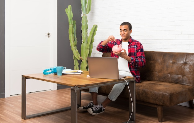 Afroamerikanermann mit laptop im wohnzimmer ein sparschwein nehmend und glücklich, weil es voll ist