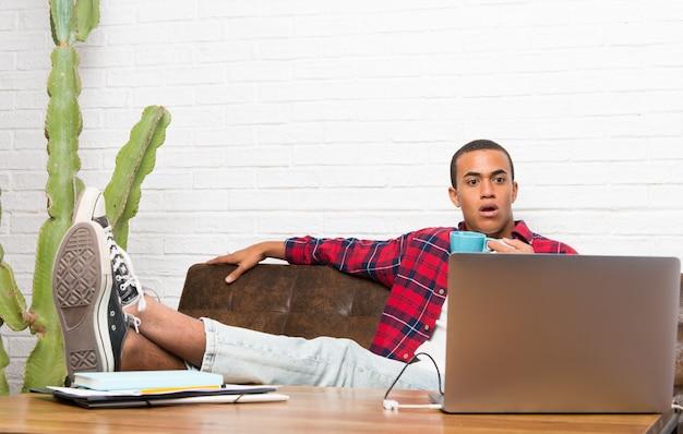 Afroamerikanermann mit laptop im wohnzimmer einen film im laptop aufpassend