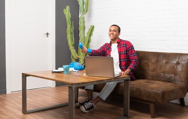 Afroamerikanermann mit laptop im wohnzimmer sprechend mit weinlesetelefon