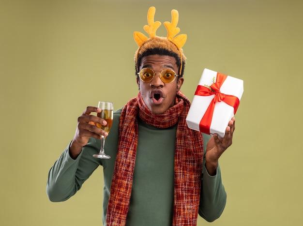 Afroamerikanermann mit lustigem rand mit hirschhörnern und schal um hals, der glas champagner und weihnachtsgeschenk hält, das kamera betrachtet, die über grünem hintergrund steht