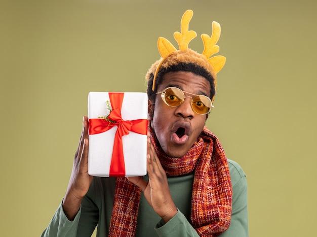 Afroamerikanermann mit lustigem rand mit hirschhörnern und schal um hals, der weihnachtsgeschenk hält, das kamera betrachtet und erstaunt über grünem hintergrund steht