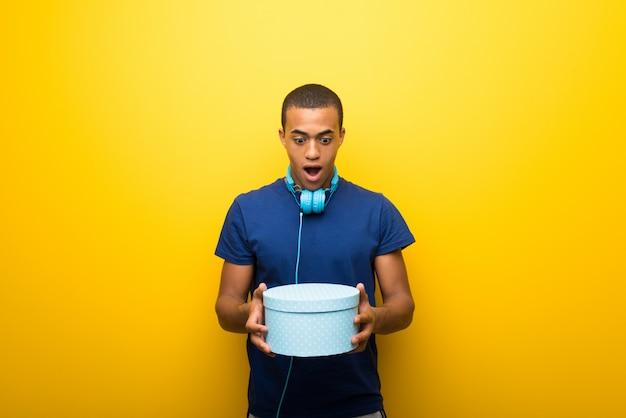Afroamerikanermann mit t-shirt auf dem halten von geschenkboxen in den händen