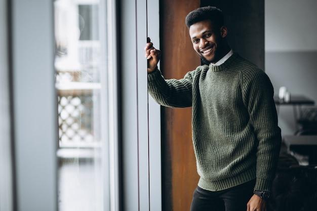 Afroamerikanermann mit telefon in einem café