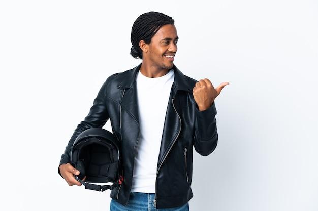 Afroamerikanermann mit zöpfen, die einen motorradhelm auf weiß halten, der zur seite zeigt, um ein produkt zu präsentieren