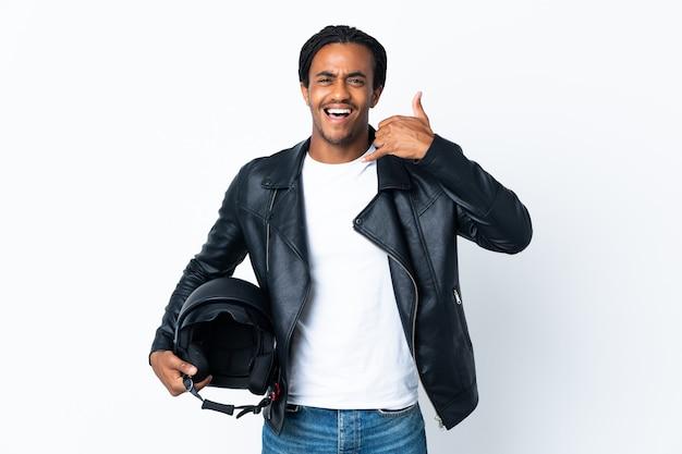 Afroamerikanermann mit zöpfen, die einen motorradhelm lokalisiert auf weißem hintergrund halten, der telefongeste macht. rufen sie mich zurück zeichen