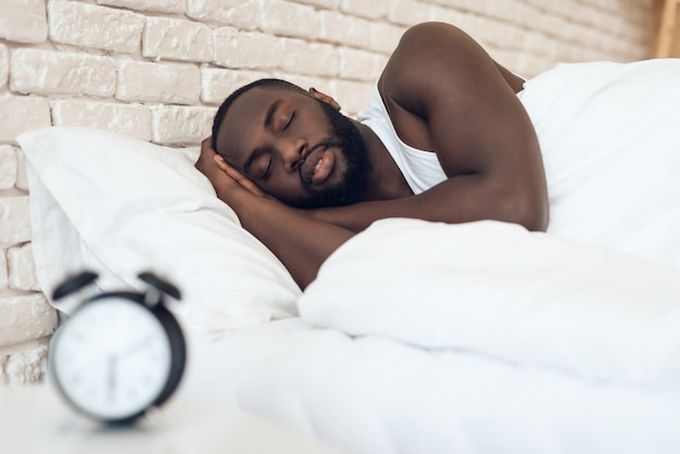 Afroamerikanermann schläft im bett nahe bei wecker