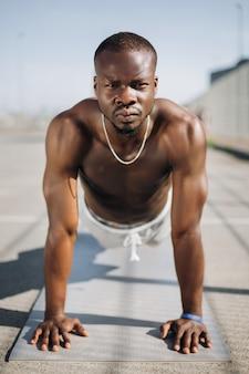 Afroamerikanermann steht auf seinen armen aus den grund, die stoßups tun