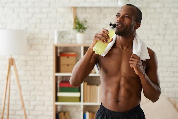 Afroamerikanermann trinkt saft von der flasche nach der ausbildung