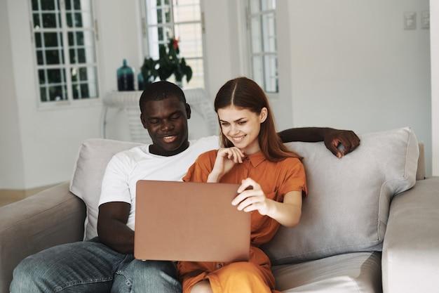 Afroamerikanermann und kaukasische frau, die den laptop zu hause benutzen