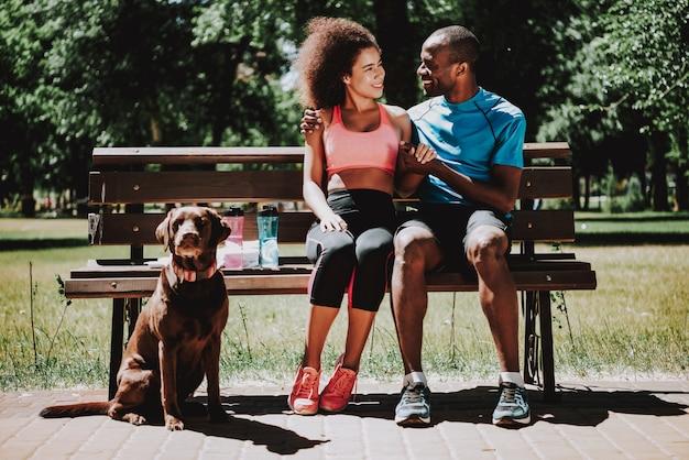 Afroamerikanermann und nettes mädchen auf parkbank