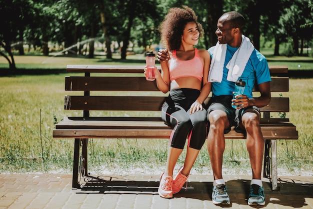Afroamerikanermann und nettes mädchen auf parkbank.