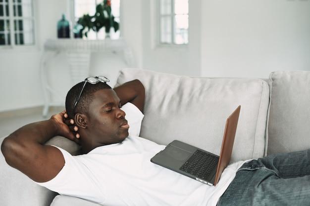 Afroamerikanermann zu hause, der film auf laptop sieht