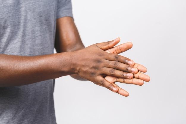 Afroamerikanermannhände unter verwendung des waschhanddesinfektionsgelpumpenspenders zum schutz von keimen und bakterien