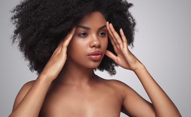 Afroamerikanermodell, das gesichtshaut massiert