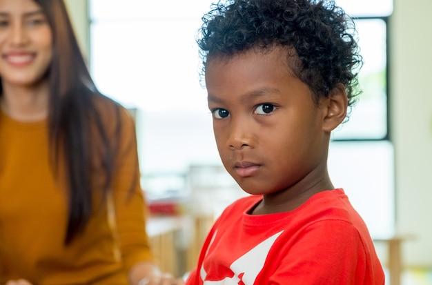 Afroamerikanernaturkind mit dem lehrer, der am hintergrund im kindergartenklassenzimmer lächelt