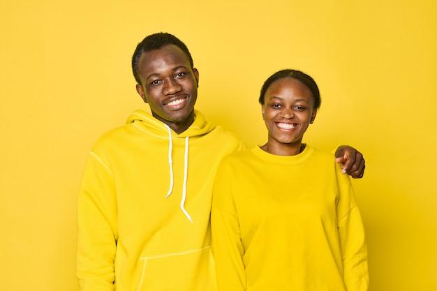 Afroamerikanerpaar auf gelben kapuzenpullis