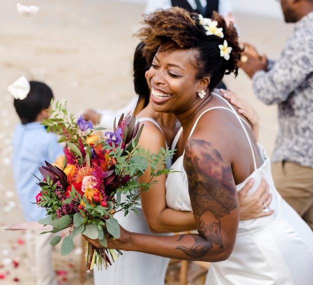 Afroamerikanerpaare, die am strand heiraten