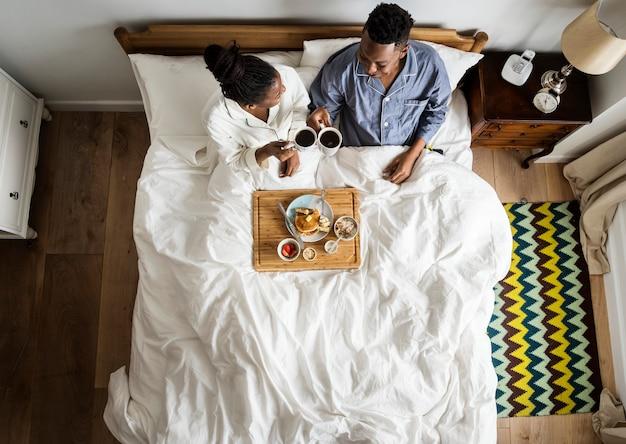 Afroamerikanerpaare im bett, das im bett frühstückt