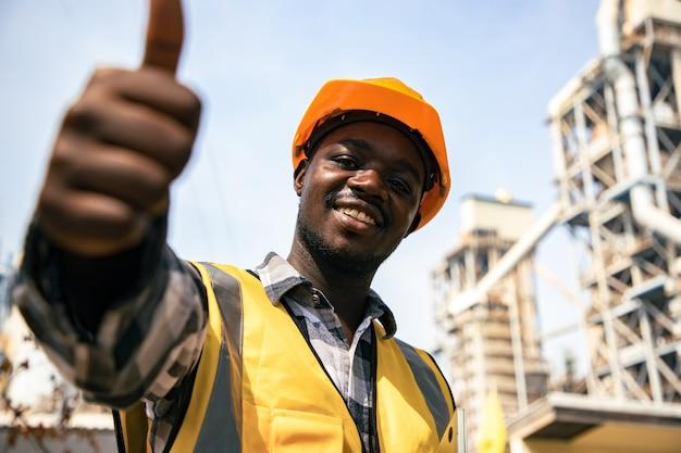 Afroamerikanerporträt des jungen lächelnden bauingenieurarbeiters, der schutzhelm trägt, bevor zur arbeitsstelle gehen