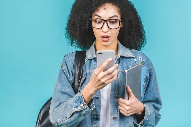 Afroamerikanerschwarz schockierte verblüffte studentin, die smartphone verwendet, das über lokalisiert über blauem hintergrund steht.