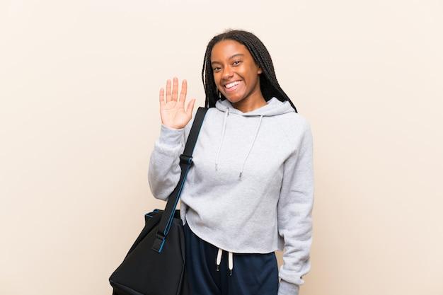 Afroamerikanersport-jugendlichmädchen mit dem langen umsponnenen haar begrüßend mit der hand mit glücklichem ausdruck