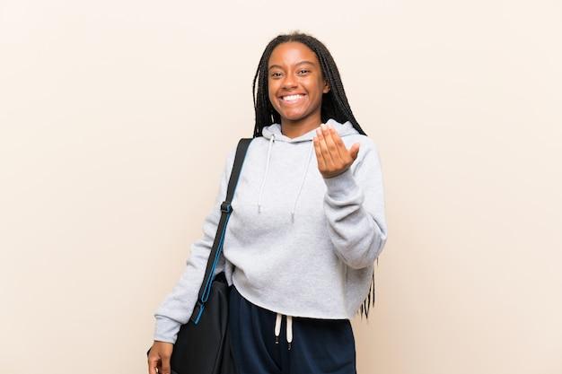 Afroamerikanersport-jugendlichmädchen mit dem langen umsponnenen haar, das einlädt, mit der hand zu kommen. schön, dass sie gekommen sind
