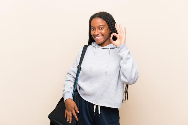 Afroamerikanersport-jugendlichmädchen mit dem langen umsponnenen haar, das okayzeichen mit den fingern zeigt