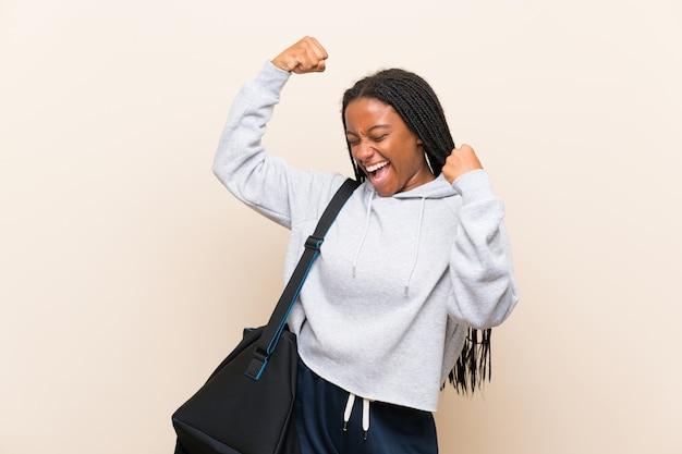 Afroamerikanersport-jugendlichmädchen mit dem langen umsponnenen haar einen sieg feiernd