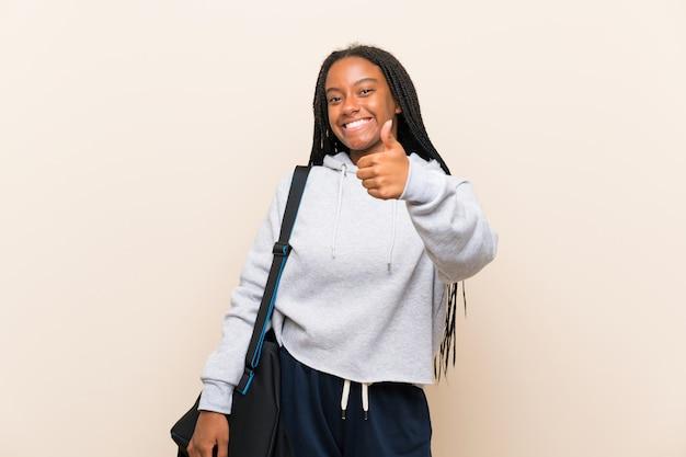 Afroamerikanersport-jugendlichmädchen mit dem langen umsponnenen haar mit den daumen oben, weil etwas gutes geschehen ist